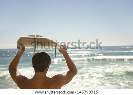Rear view of young man carrying surfboard above head by ocean