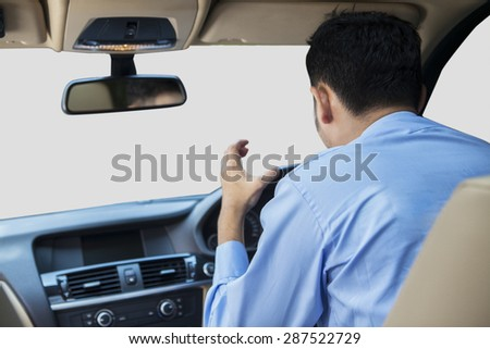 Rear view of young man driving a car and looks angry, shouting inside the car - stock photo