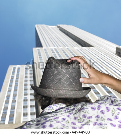 Rear view of young man looking up at skyscraper. Vertical shot. - stock photo