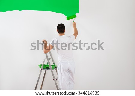 Rear view of young man painting wall with green paint roller at home - stock photo