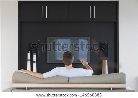 Rear view of young man using remote control while sitting on couch in living room - stock photo