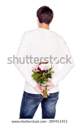 Rear view of young man wearing blue jeans and white long sleeve, holding bunch of flowers behind his back isolated on white background - dating concept