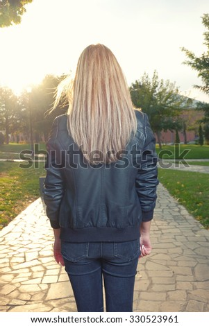 Rear view of Young pensive woman looking at setting sun