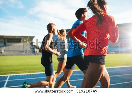 Rear view of young people running together on race track. Young athletes practicing a run on athletics stadium track. - stock photo
