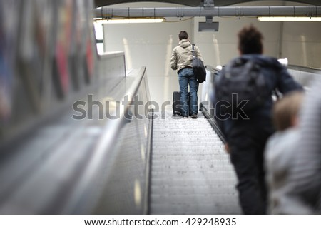 Rear view of young people with baggage standing on the up escalator - stock photo
