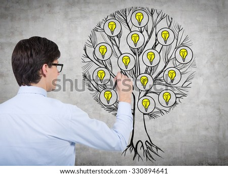 Rear view of young professional who is drawing a tree with light bulbs on the concrete wall. Light bulbs as a concept of new business ideas. - stock photo