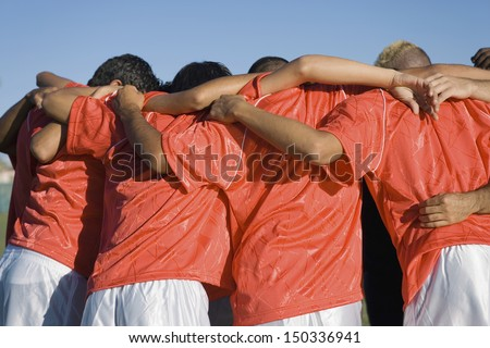 Rear view of young soccer players discussing strategy - stock photo