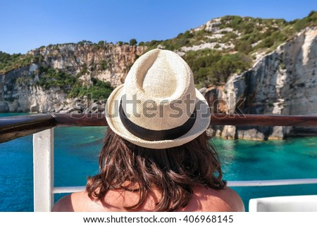 Rear view of young woman enjoying warm sunny day on the cruise, with a white hat. Blue caves in Zakynthos Island - stock photo