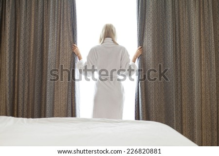 Rear view of young woman in bathrobe opening window curtains at hotel room - stock photo
