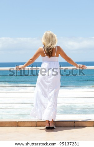 rear view of young woman in white dress looking at seascape