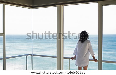 Rear view of young woman looking at sea view from balcony at resort - stock photo