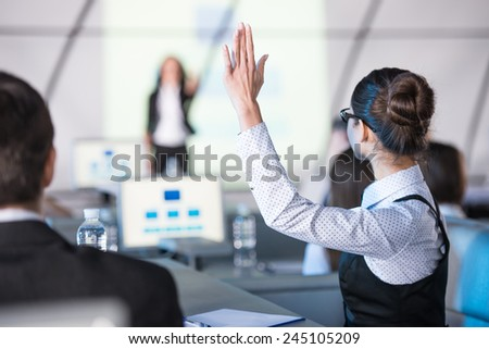 Rear view of young woman raised her hand during presentation. - stock photo