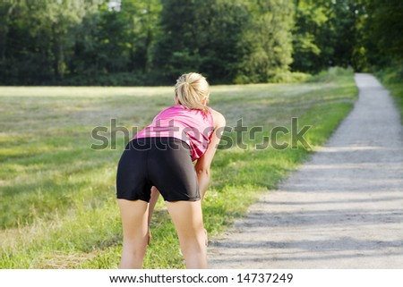Rear view of young woman resting on pathway. Copy space - stock photo