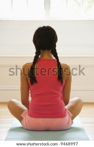Rear view of young woman sitting on mat with legs crossed in yoga pose. - stock photo