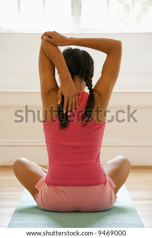 Rear view of young woman sitting on mat with legs crossed stretching. - stock photo