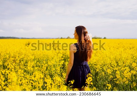 Rear view of young woman with hand in long hair on yellow blooming rapeseed field - stock photo