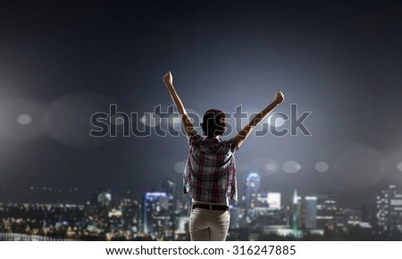 Rear view of young woman with hands up looking at night city - stock photo