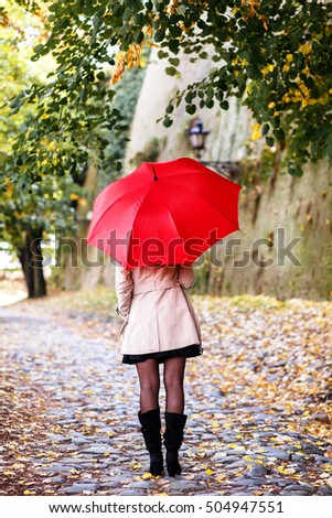 Rear view of young woman with red umbrella.