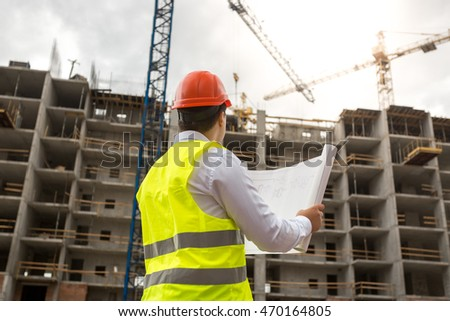 Rear view on engineer on building site examines blueprints