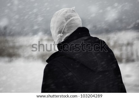 Rear view on the human with bandaged head under the nuclear snowstorm - stock photo