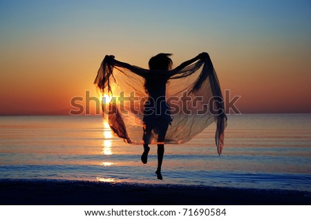 Rear view on the silhouette of the woman jumping at the beach during sunset. Natural darkness and colors - stock photo