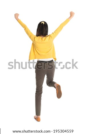 Rear view or back of an Asian girl arms up happy jumping around, full length standing isolated on white background. - stock photo