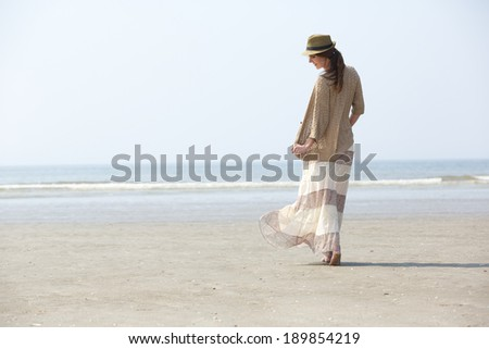 Rear view portrait of a beautiful woman walking on the beach - stock photo