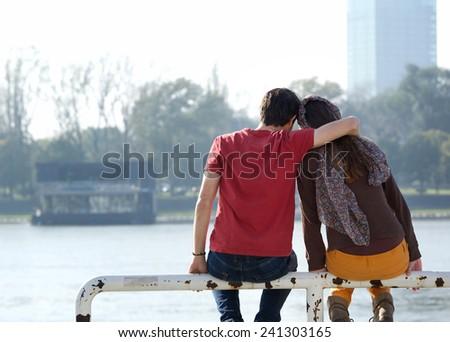 Rear view portrait of a boyfriend and girlfriend sitting outdoors  - stock photo