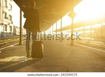 Rear view portrait of a man standing with bag and mobile phone at train station - stock photo