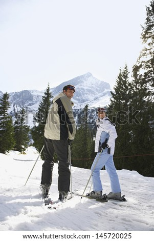 Rear view portrait of a skiing couple standing on ski slope - stock photo