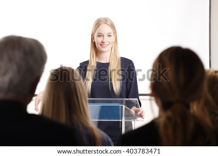 Rear view portrait of large group of business people at seminar. Focus is on blond businesswoman while giving a presentation in a conference.