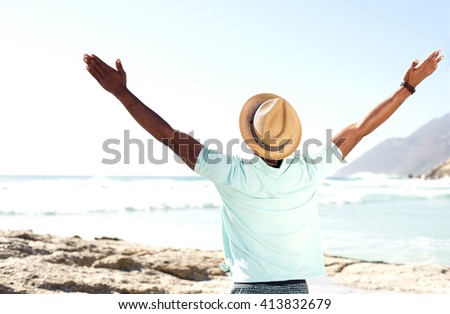 Rear view portrait of man with at standing at the beach with his hands wide open towards the say - stock photo