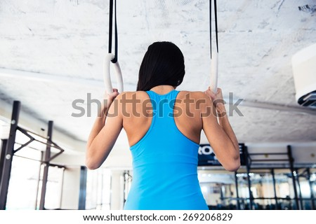 Rear view portrait of woman working out on gimnastic rings at gym - stock photo