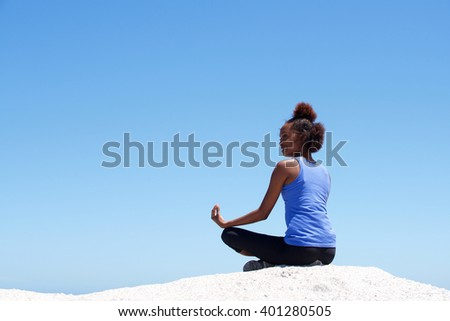 Rear view portrait of young african woman sitting in yoga pose on the rock against blue sky - stock photo