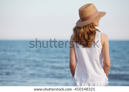 Rear view shot of a woman standing on a sandy beach while wearing straw hat.