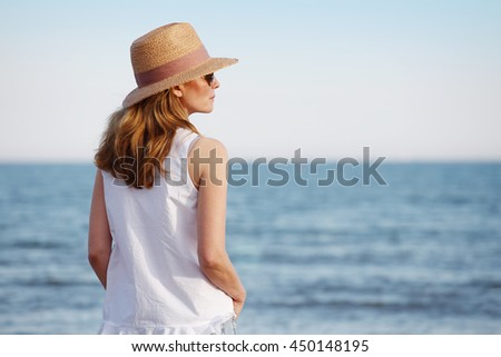 Rear view shot of a woman wearing casual clothes and straw hat while standing by the sea.
