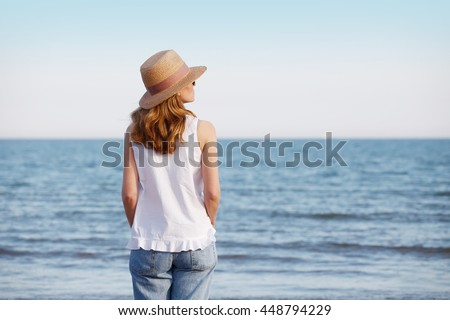 Rear view shot of a woman wearing straw hat and sunglasses while standing and relaxing on the beach while on summer vacation.
