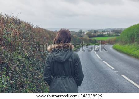 Rear view shot of a young woman walking on a country road by herself in the autumn or winter - stock photo