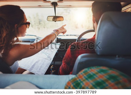 Rear view shot of couple driving on country road. Woman holding map and showing the route map to her boyfriend driving the car. Couple on a road trip. - stock photo