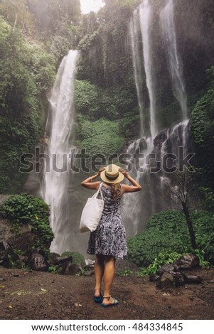 Rear view shot of female tourist admiring beautiful waterfall in tropical rain forest. Young woman looking at waterfall.