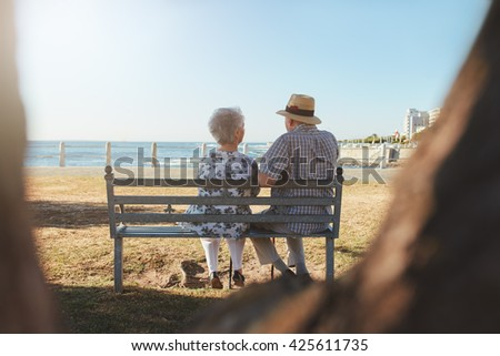 Rear view shot of senior couple sitting on a bench outdoors and looking at the sea. - stock photo