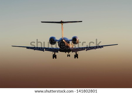 rear view silhouette of private corporate jet in flight at sunset