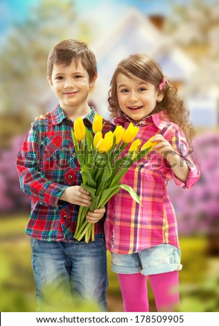 Rear view son with bunch of beautiful tulips behind back preparing nice surprise for his mother . Mothers day concept - stock photo
