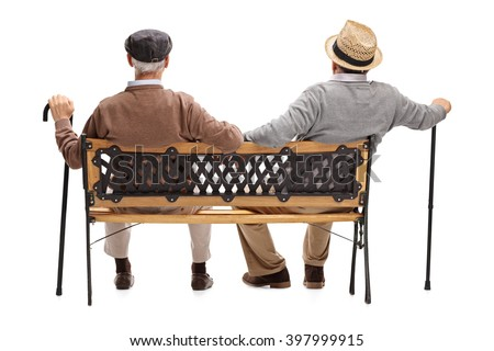 Rear view studio shot of two relaxed senior gentlemen sitting on a wooden bench isolated on white background - stock photo