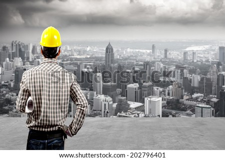 rear view technician builder in protective safety equipment goggles hard hat and and blueprints against balcony overlooking city dusky before rain falling - stock photo