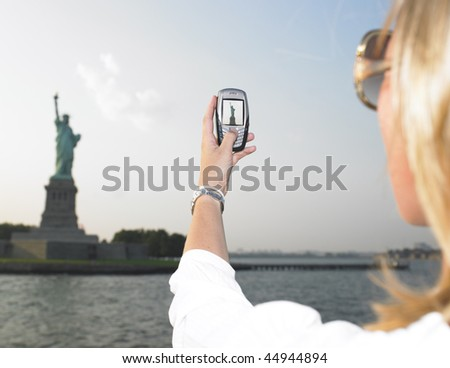 Rear view woman using a mobile phone to take a picture of the Statue of Liberty.  Horizontal shot. - stock photo