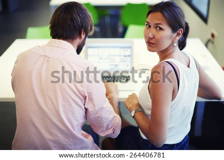 Rear view young asian woman looking to the camera, couple of freelancers sitting at the desk with laptop in modern office space, couple of students learn in big light library with books and net-book - stock photo
