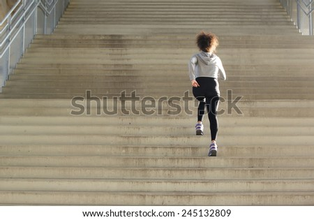 Rear view young female athlete running up stairs - stock photo