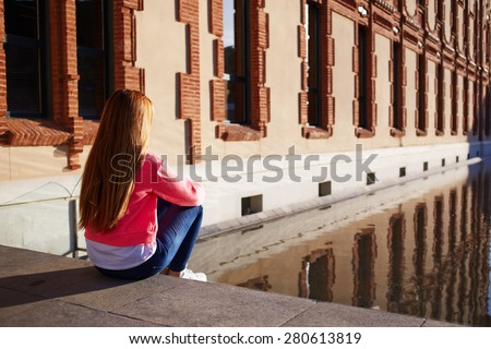 Rear view young female looking thoughtful as sitting on the steps alone, young woman suffering from loneliness and depression, trendy hipster enjoying sunny afternoon outdoors, teenager relaxing - stock photo