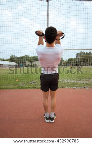 Rear view young muscular man  suspension training similar to trx